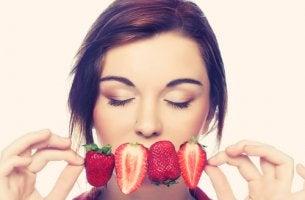 Mujer oliendo fresas