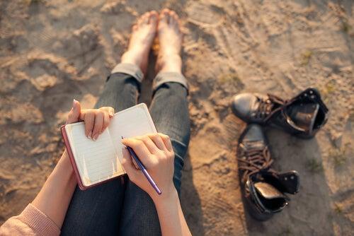 Mujer sentada escribiendo intentando transformar pensamientos negativos en positivos