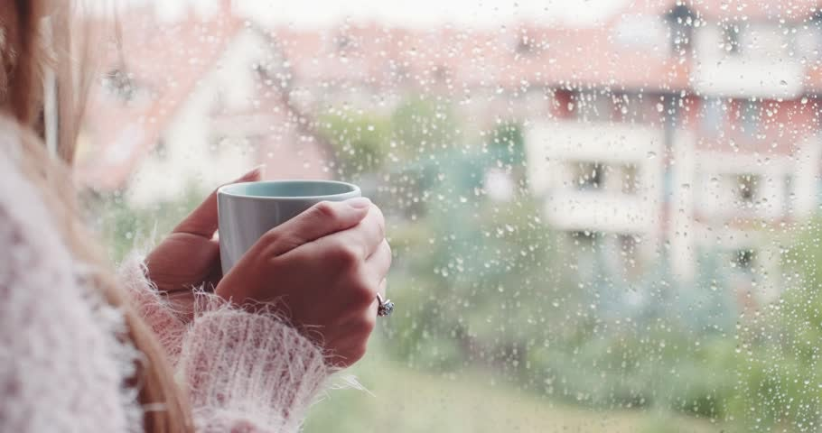mujer con taza de té escuchando el sonido de la lluvia