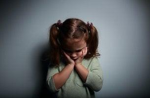 Niña triste por tener padres ausentes emocionalmente