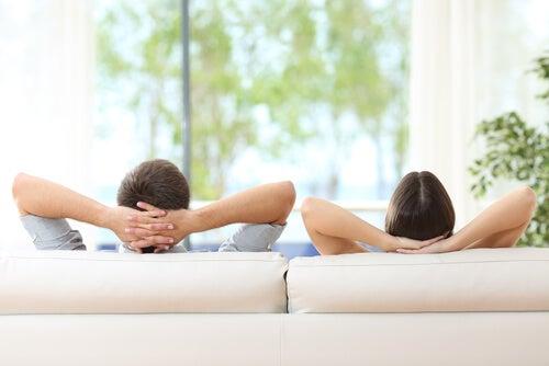 Pareja descansando tumbados en el sofá