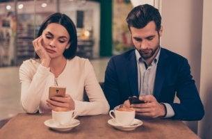 Pareja mirando sus móviles sin hablar