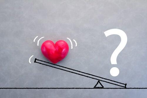 Balanza con un corazón y una interrogación para representar la inseguridad en el amor