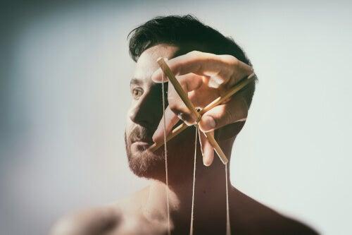 Cabeza de un hombre con manos manipulando hilos