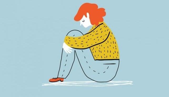 chica sentada en el suelo representando las diferencias entre tristeza y depresión