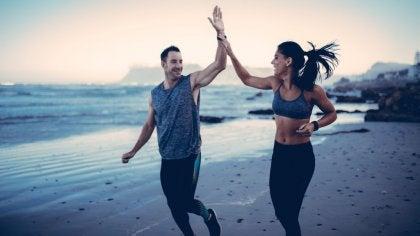 Chico y chica chocando sus manos mientras hacen deporte