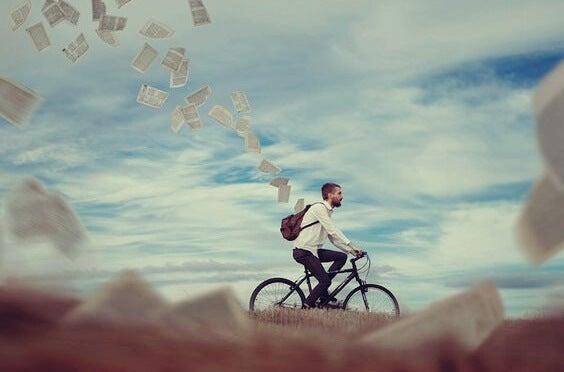 chico en bici dejando ir papeles simbolizando esos momentos cuando nadie cree en ti