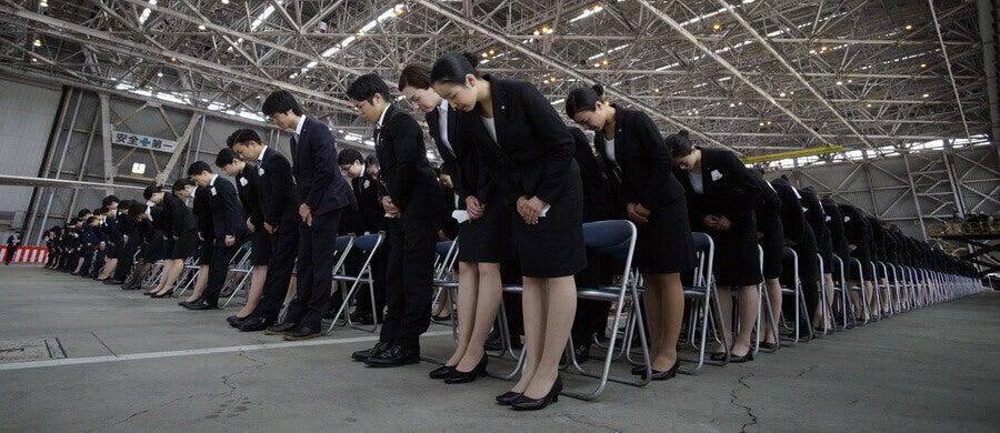 Empleados uniformados bajando la cabeza para saludar