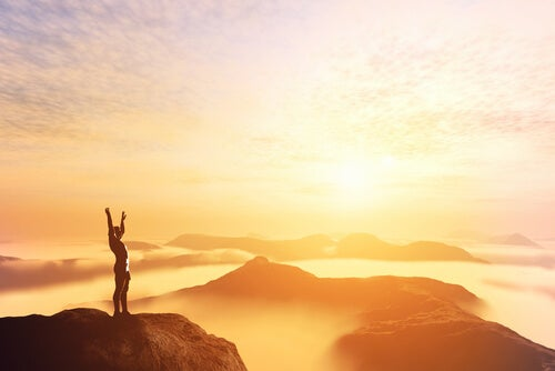 Hombre en la cima de la montaña pensando en que debemos esforzarnos por la excelencia
