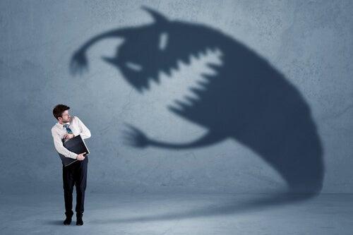 Hombre con miedo a una sombra de monstruo para representar los miedos comunes