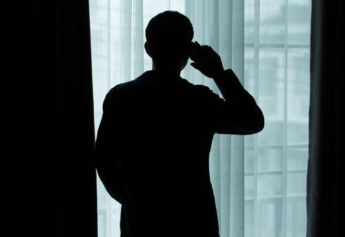 Hombre mirando por la ventana mientras habla por teléfono