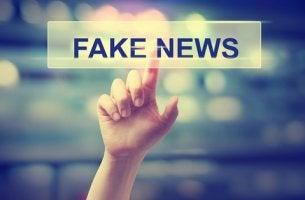 Mano señalando un cartel en el que pone Fake News