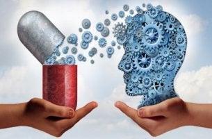 Manos con una pastilla y el perfil de la cabeza de una persona para representar los efectos de las benzodiacepinas