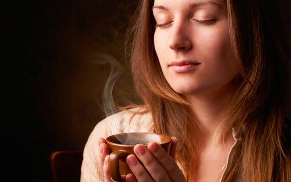 mujer con la taza en la mano disfrutando del olor a café