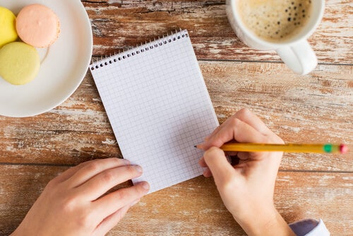 Mujer escribiendo objetivos en una libreta