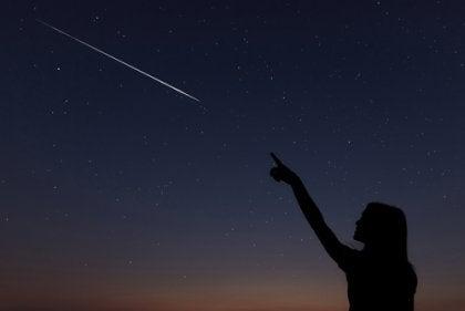 Mujer pidiendo un deseo al pasar una estrella fugaz