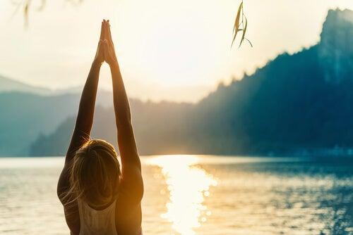 Mujer haciendo la postura de las manos levantados