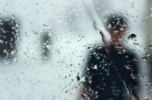 Silueta de un hombre tras un cristal con lluvia