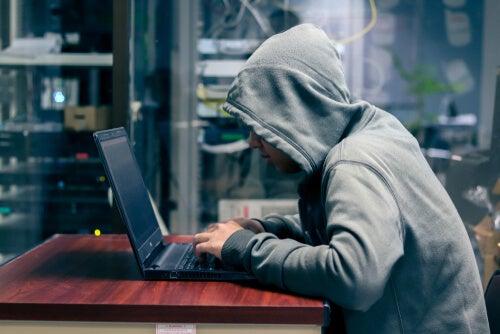 Hombre con una capucha frente a un ordenador