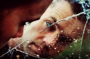 hombre tras cristal roto simbolizando el síndrome delirante