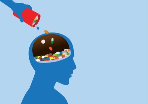 Mano vertiendo un bote de pastillas en la mente de una persona