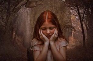 Manos que atrapan a una niña pelirroja mientras piensa en sus miedos más frecuentes