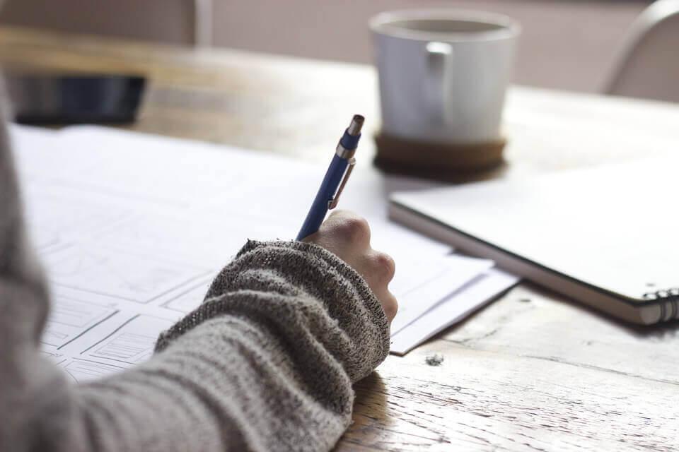 Mujer escribiendo normas morales en un cuaderno