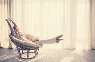 Mujer estirándose en una silla mientras piensa en llevar una vida minimalista