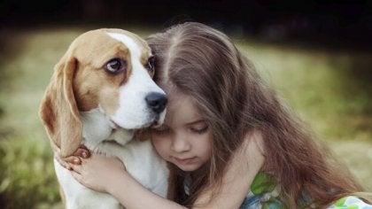 Niña abrazando a su perro para representar la empatía en las personas con síndrome de Asperger