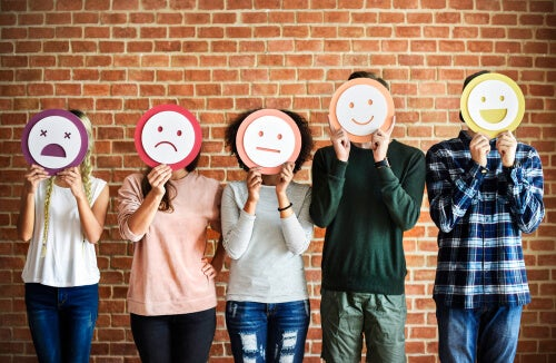 Personas con dibujos de emociones sobre sus caras