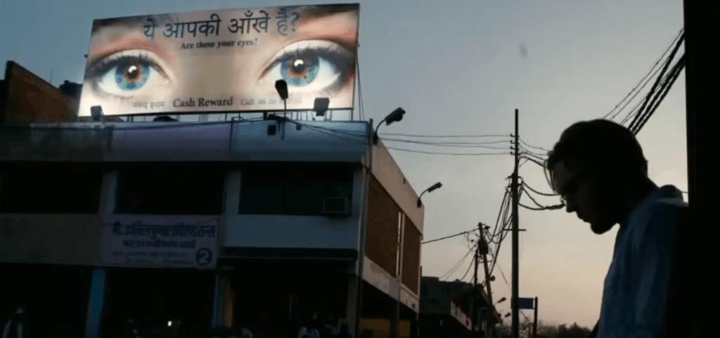 Hombre frente a un cartel con ojos
