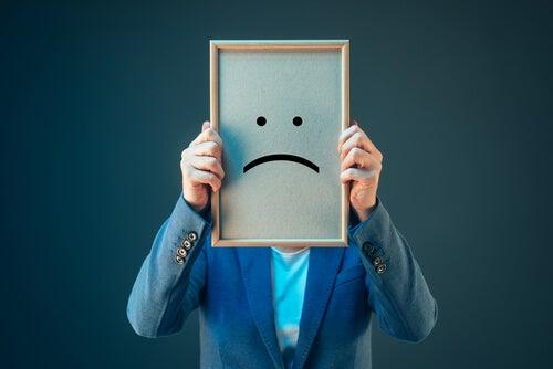 Hombre sujetando un cuadro con una cara triste