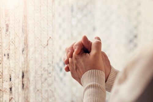 Manos de una persona mayor rezando