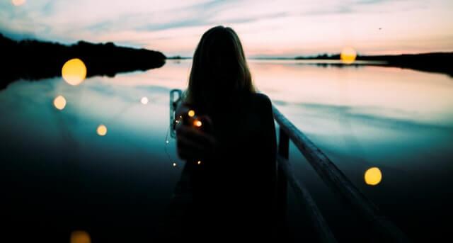 Mujer de espaldas mirando un río pensando en la magia de la conexión