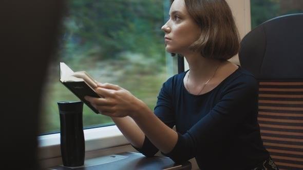 chica en tren para representar los beneficios de leer mientras viajamos