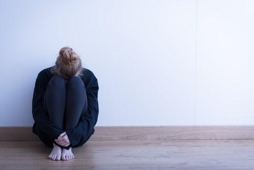 Mujer triste con la cabeza entre las piernas
