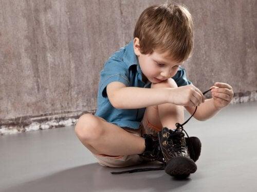 Niño atándose los cordones de los zapatos