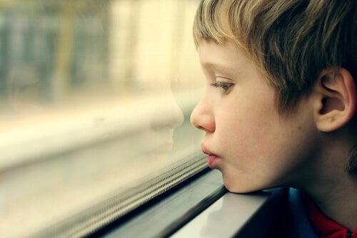 Niño autista mirando por la ventana