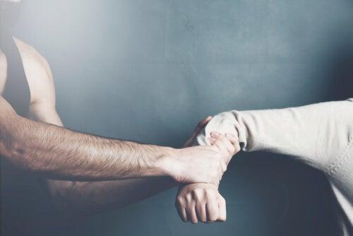 Hombre agarrando el brazo a una mujer