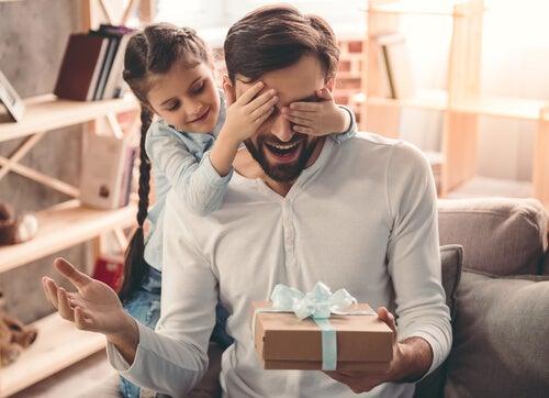 Niña tapando los ojos a su padre para darle un regalo