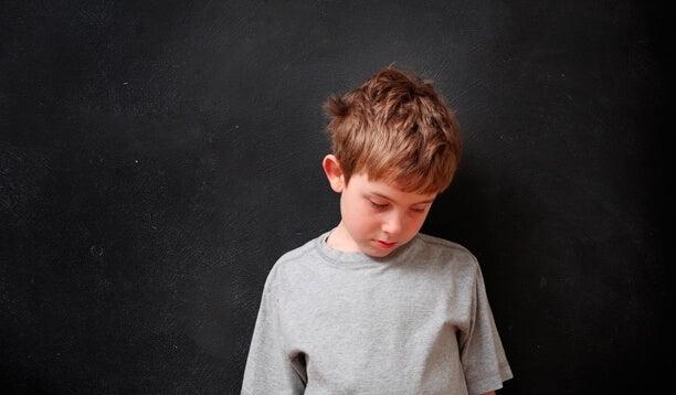 Niño triste mirando hacia abajo