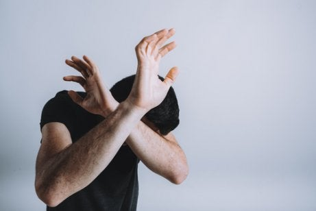Hombre cruzando los brazos por miedo