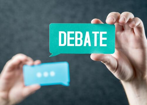 Mano sujetando el cartel con la palabra debate