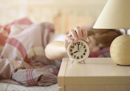 Mujer con dysania apagando el despertador