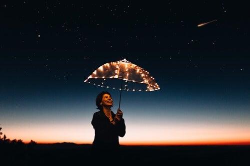 mujer feliz con paraguas simbolizando la belleza de ser tú