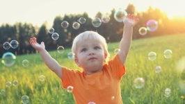 Niño jugando con pompas de jabón