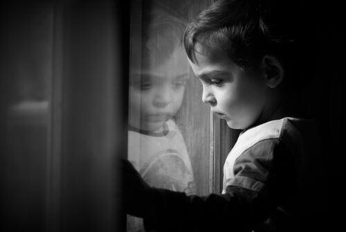Niño mirando por una ventana simbolizando las secuelas del abuso sexual