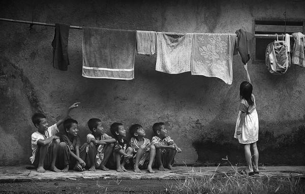 Niños mirando a una niña coger ropa