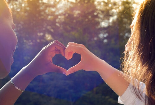 Amigas haciendo una forma de corazón con las manos