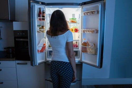 Mujer con síndrome de ingesta nocturna delante del frigorífico